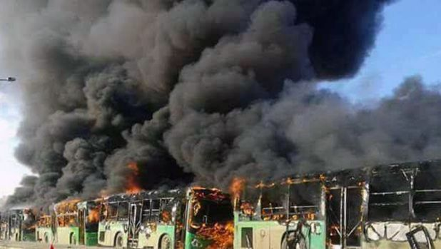 Smoke rises from green government buses awaiting to evacuate residents in Idlib province, Syria on Sunday.