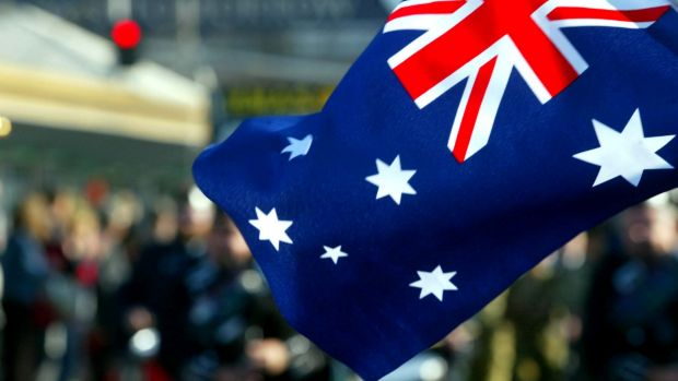 Crowd members wave an Australian flag as marchers go past on Swanston St during the ANZAC day march in Melbourne 2003.