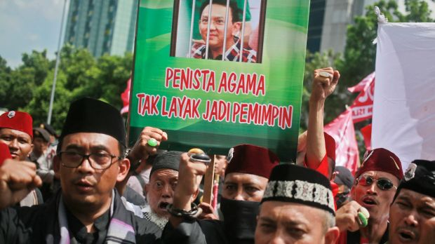 """Muslim protesters shout slogans as they hold up a placard with a picture depicting Jakarta governor Basuki """"Ahok"""" ..."""