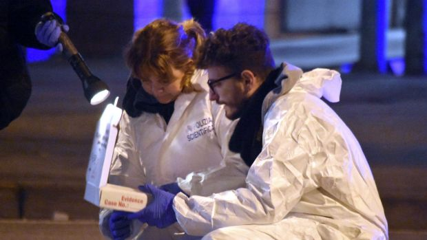 Italian forensic police collect evidence in an area after a shootout between police and a man near a train station in ...