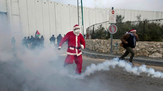 A Palestinian protester dressed as Santa Claus runs to avoid tear gas during clashes in the West Bank city of Bethlehem.