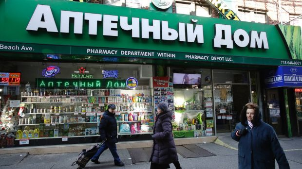 People walk past a pharmacy that caters to the Russian community in Brooklyn, New York. Russian-speaking expatriates in ...
