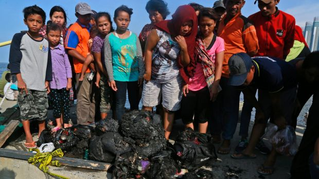 People at Muara Angke Port in Jakarta, Indonesia, inspect charred personal belongings of passengers on a ferry that ...