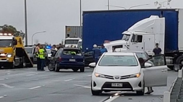 A truck jack-knifed on the M1 Motorway, with several cars damaged and traffic building.