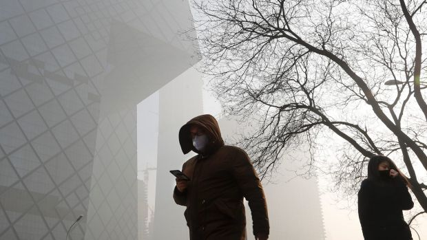 People wearing protection masks walk near the iconic headquarters of China's state broadcaster Central China Television ...