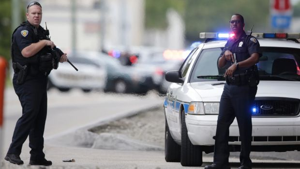 Police officers stand on the perimeter road along the Fort Lauderdale-Hollywood International Airport.