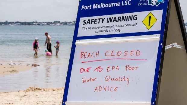 Port Melbourne beachgoers escape the heat on Saturday and go for a a swim despite warning signs from EPA Victoria.