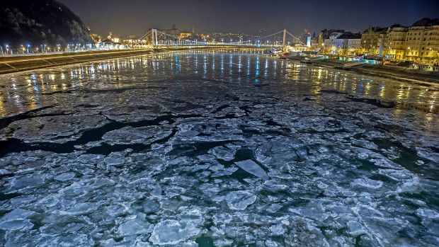 Ice floes float in the water of River Danube at the Szabadsag (Freedom) Bridge in Budapest, Hungary.