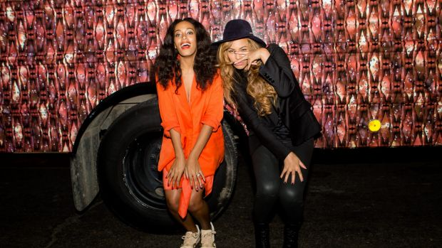 """Solange Knowles (L) and Beyonce Knowles pose for a photo against the bounce bus at the cocktail reception for """"Amen ..."""