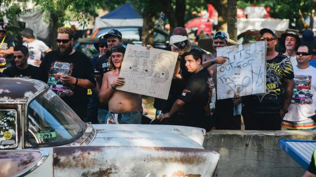 Men hold up signs along Tuff Street during Summernats 2017.