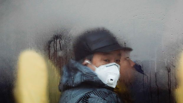 A man wearing a mask looks out from a bus in Beijing as the capital of China is blanked by smog.
