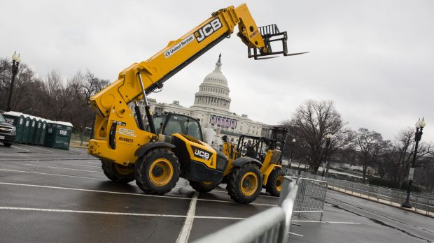 A forklift stands in front of security fences near the US Capitol building. Reported inauguration plans such as a parade ...