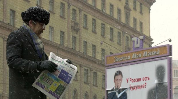 A man hands out free advertising newspapers in Moscow while behind him looms the Federal Security Service building. The ...