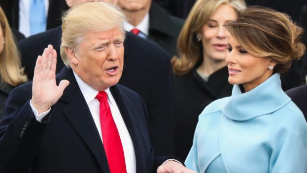 Donald Trump, watched by his wife Melania, is sworn in as the 45th president of the United States.