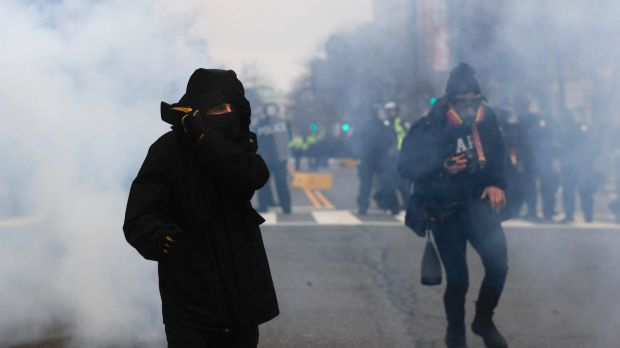 Anonymous no more?: A protester shields his mouth and nose from gas fired by police during a demonstration after the ...