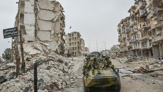 Russian troops in the devastated Syrian city of Aleppo.