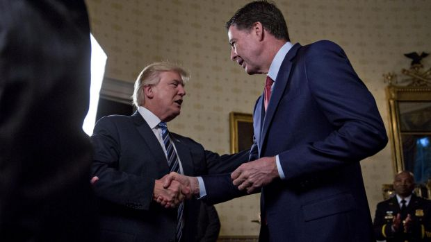 President Donald Trump greets then-FBI director James Comey with a handshake, before pulling him in for a hug.