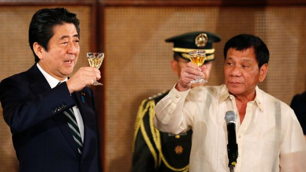 Japanese Prime Minister Shinzo Abe, left, and Philippine President Rodrigo Duterte toast during a state banquet at the ...