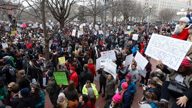 Protesters carry signs and chant in Lafayette Park near the White House during a demonstration to denounce President ...