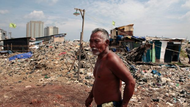 A Kampung Akuarium residents walks through mountains of rubbish and rubble in the makeshift neighbourhood.