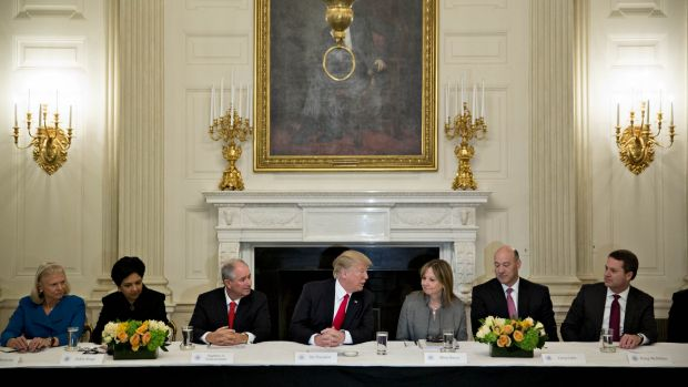Happier days: Donald Trump meets with business leaders at the White House. Almost all have now abandoned him.