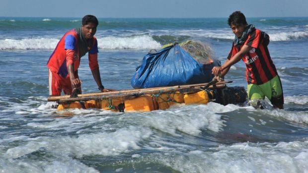 Rohingya fishermen pull a raft made of empty plastic containers along the coastline of the Bay of Bengal in Maungdaw, ...