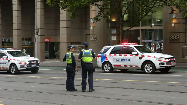 Police outside the AFP building on La Trobe Street on Monday evening.