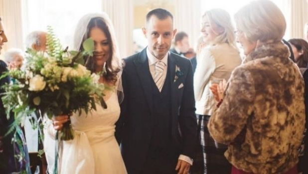 Angelia Cuming and her husband Paul walk down the aisle on their wedding day.