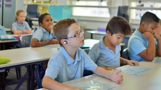 Perth school boy Kai finds it easier to concentrate on the teacher's voice with Nuheara's IQbuds helping to compensate ...