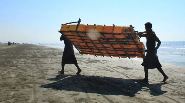 Rohingya fishermen carry a fishing raft, constructed with empty plastic containers, up the beach in Maungdaw, western ...
