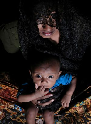 Mohsena Begum, a Rohingya who escaped to Bangladesh from Myanmar, holds her child at an unregistered refugee camp in ...