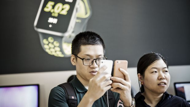 A customer inspects iPhone 7 models in a Shanghai shopping mall.