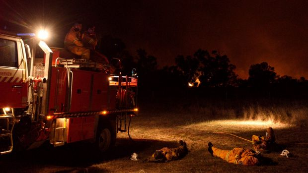 NSW RFS crew members from Cumberland Strike Team take a well earned rest after a long day of fighting a large grass fire ...