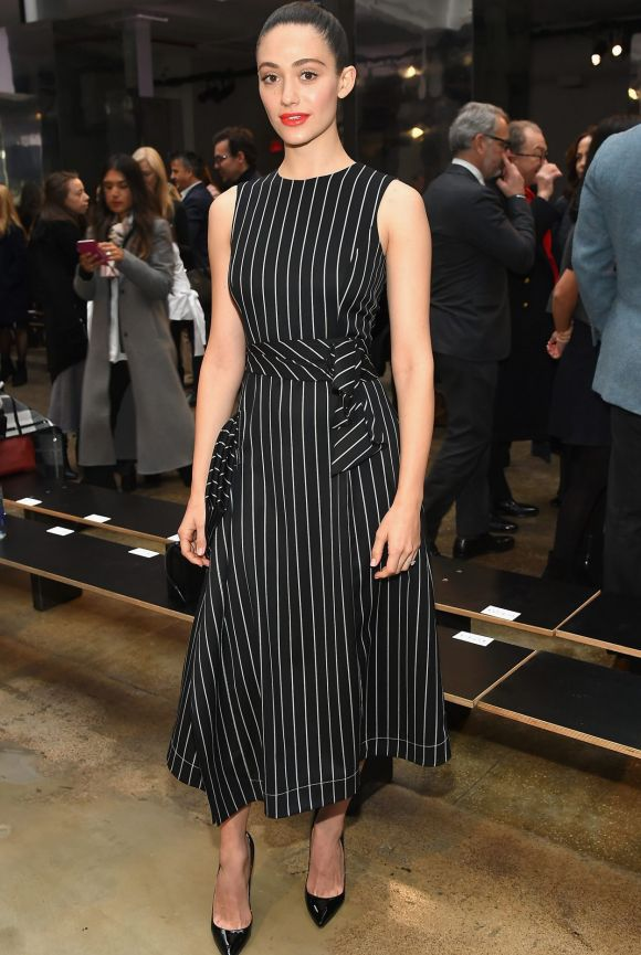 Actress Emmy Rossum was radiant at the Carolina Herrera Collection show with a simple pin-stripe dress matched with ...