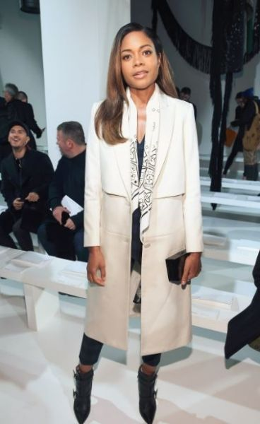 Naomie Harris paired her cream tailored coat with the white bandanna sent around by Calvin Klein as part of the ...