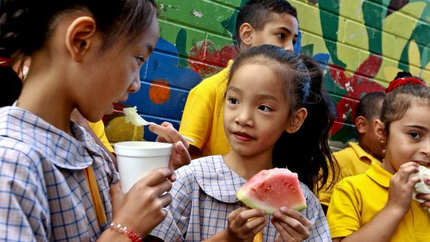 Cabramatta Public School children eat rice pudding and watermelon supplied by Foodbank.