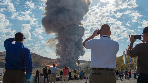 Spectators watch the second and final qualification motor test for the Space Launch System's booster.