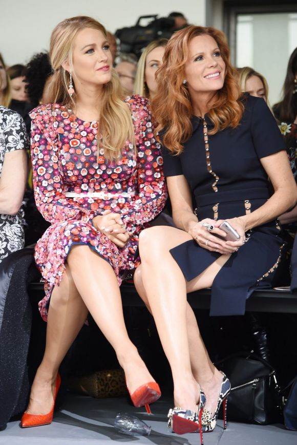 Sisters Blake Lively (L) and Robyn Lively opt for matching crossed legs and Louboutins at the Michael Kors Collection ...