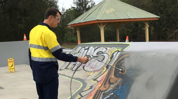 Lord Mayor Graham Quirk paints over graffiti at the council's Stafford Heights skate park.