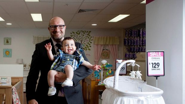 Hands full: Baby Bunting CEO Matt Spencer posing for a photo with baby Oscar James Parnall before the retailer's ...