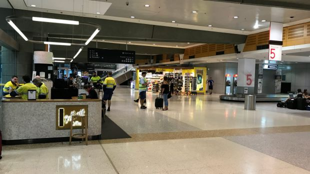 Qantas ground crews in a deserted domestic terminal, as a storm hits Sydney.