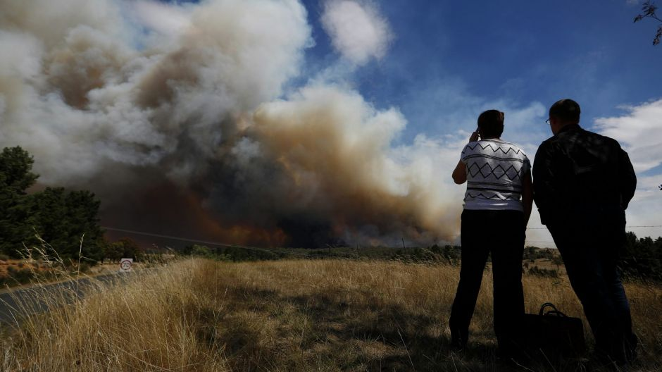 Pip Wyrdeman observes the fire where her dad's home is, during a fire at Carwoola, southeast of Canberra.