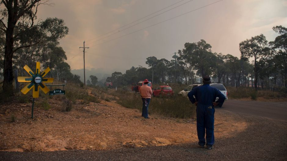 Vanessa and Kevin Lesley watch on as the fire burns in the distance, shortly before their own property was destroyed.