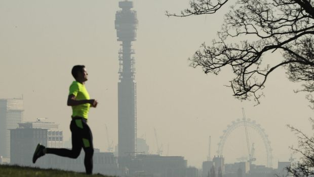 A jogger in Primrose Hill as smog covers the London skyline on January 24, 2017.