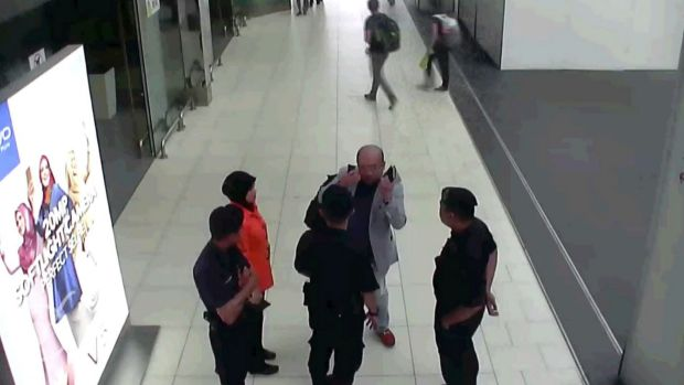 In this image from security camera footage, Kim Jong-nam, in grey, gestures towards his face while talking to airport ...