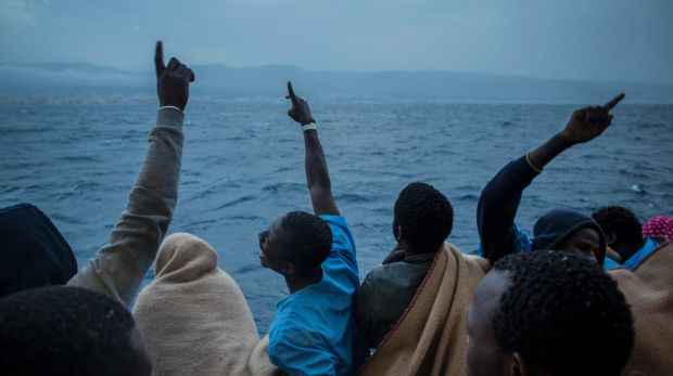 African men celebrate their arrival in Italy aboard a Spanish NGO Proactiva Open Arms ship, after being rescued off ...