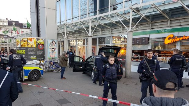 A car stands in front of a store, guarded by police in Heidelberg, Germany, on Saturday.