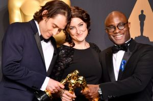 Producers Jeremy Kleiner, left, and Adele Romanski and director Barry Jenkins pose after <i>Moonlight</i> was awarded ...