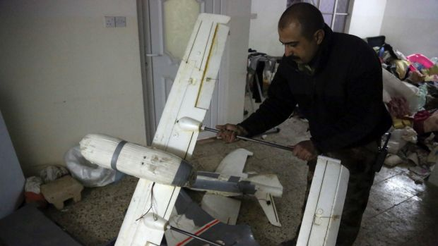 An Iraqi officer inspects drones belonging to Islamic State militants in Mosul.