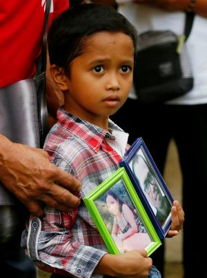 Adrian Perigrino holds portraits of his parents, both victims of extra-judicial killing, in suburban Paranaque city ...
